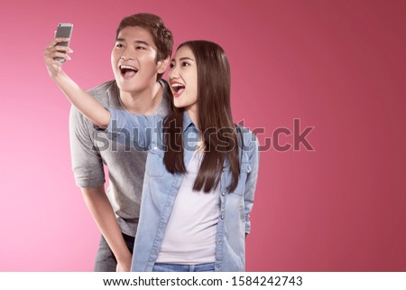 Asian couples making a selfie with a funny face using a camera phone. Valentines day #1584242743