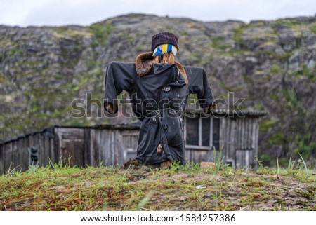 Russia, Arctic, Kola Peninsula, Barents Sea, Teriberka: Scarecrow with uniform coat in front of run down abandoned wooden houses in the city center of the old Russian settlement small fishing village. #1584257386