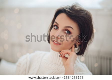 Beautiful woman in white sweater at home #1584258178