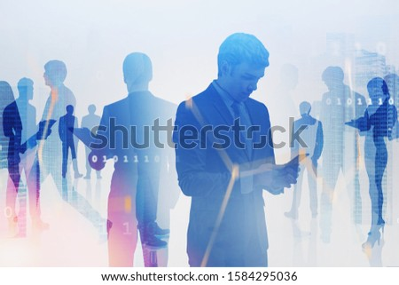 Young manager with smartphone and business people work together in city with double exposure of blurry network interface. Concept of hi tech and teamwork. Toned image #1584295036