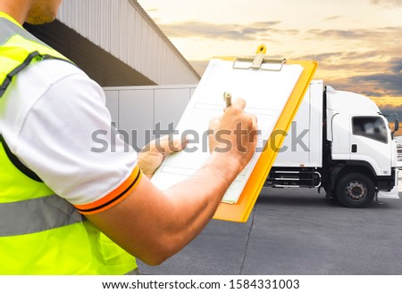 Warehouse worker holding clipboard inspecting load cargo shipment, the truck container docking load shipment goods at distribution warehouse. #1584331003