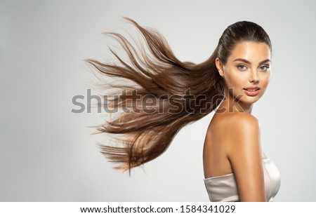 Portrait of a beautiful woman with a long straight hair. Young  brunette model with  beautiful hair - isolated on white background. Young girl with hair flying in the wind. #1584341029