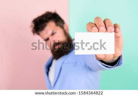 blank piece of paper. barbershop concept. best barber master. barber shop for gentlemen. brutal male beauty. serious bearded man business card. copy space. selective focus. man hold credit card.