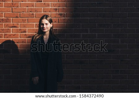 Young brunette girl with brunette loose hair dressed in black jacket looking at the cameram brick wall on the background, outdoor photo #1584372490