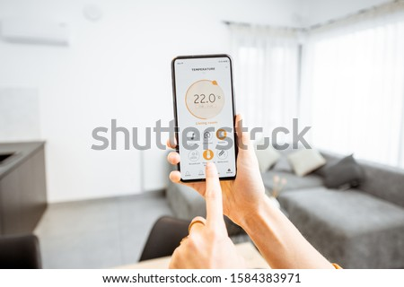 Controlling home heating temperature with a smart home, close-up on phone. Concept of a smart home and mobile application for managing smart devices at home #1584383971