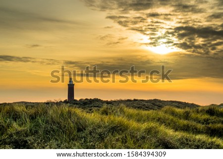 Lighthouse at Ouddorp the netherlands against a beautiful orange sky #1584394309