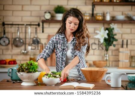 Beautiful young woman cooking in kitchen. Woman preparing pancakes. #1584395236