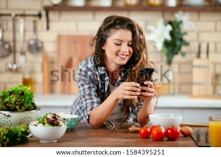 Food blogger using smartphone taking photo. Young woman photographing food in the kitchen. #1584395251
