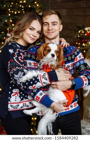 Portrait of happy spouses with their little doggie near christmas tree #1584409282