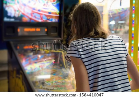 Little girl playing pinball game in theme park. Royalty-Free Stock Photo #1584410047
