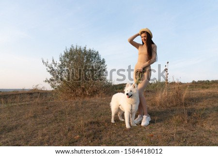Beautiful brunette girl in beige dress and hat stands with samoed dog among the field, autumn time #1584418012