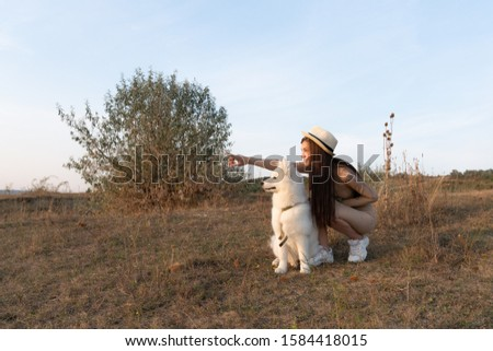 Young attractive brunette girl in beige dress and hat crouched near the samoyed puppy and pointing at left side, autumn time #1584418015