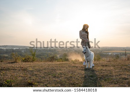 Attractive brunette girl in beige dress and hat stands among the field with samoed dog, beautiful landscape on the background, autumn time #1584418018