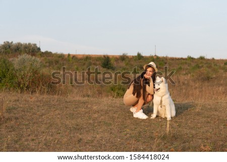 Young brunette girl in beige dress and hat crouched near the samoyed puppy, both looking at left side, autumn time #1584418024