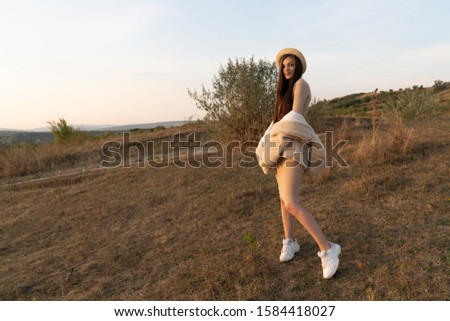 Stylish brunette girl in beige dress and hat stands among the field and posing with white coat, autumn time #1584418027
