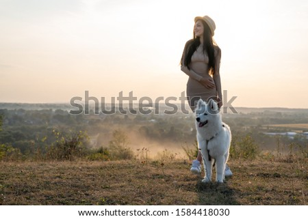 Attractive brunette girl in beige dress and hat stands among the field with samoed dog, beautiful landscape on the background, autumn time #1584418030