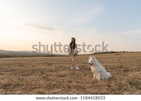 Stylish beautiful brunette girl in beige dress, coat and hat stands among the field with samoed dog on a leash, autumn time #1584418033