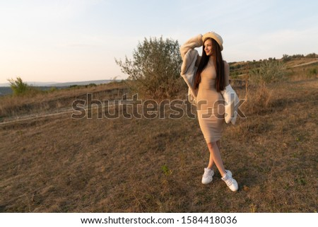 Stylish brunette girl in beige dress and hat stands among the field and posing with white coat, autumn time #1584418036