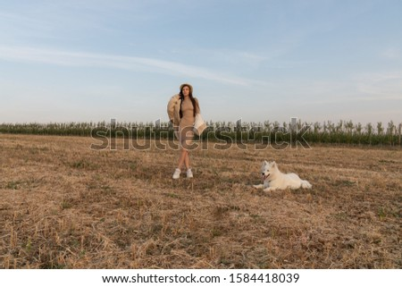 Stylish beautiful brunette girl in beige dress, coat and hat stands among the field with samoed dog on a leash, autumn time #1584418039