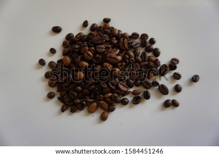 Roasted, fresh, dark coffee beans at the table ready to be ground; coffee smell is the best thing thing in the morning and espresso taste wakes you up #1584451246