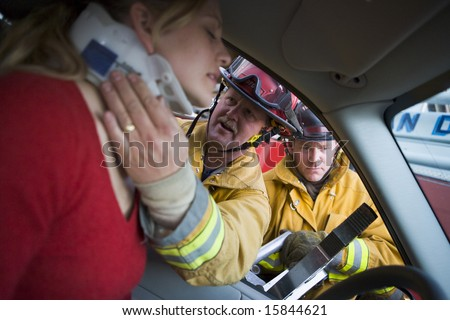 Firefighters helping an injured woman in a car #15844621