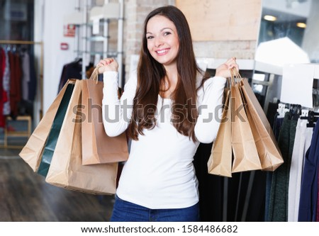 Positive cute girl  purchaser with packs delighted from purchases in the  shop
