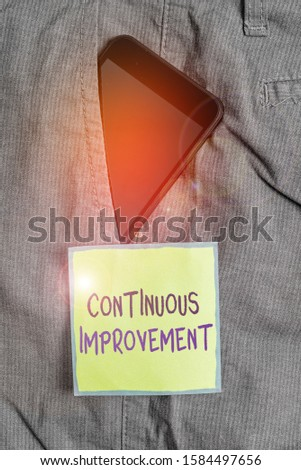 Text sign showing Continuous Improvement. Conceptual photo ongoing effort to improve products or processes Smartphone device inside formal work trousers front pocket near note paper. #1584497656