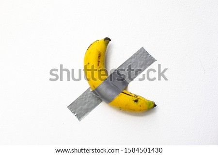duct taped banana on white wall Royalty-Free Stock Photo #1584501430