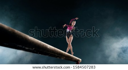 Female gymnast doing a complicated trick on gymnastics balance beam.