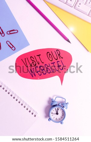 Writing note showing Visit Our Website. Business photo showcasing visitor who arrives at web site and proceeds to browse Red bubble copy space paper on the table with clock. #1584511264