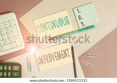 Text sign showing Continuous Improvement. Conceptual photo ongoing effort to improve products or processes Writing equipments and computer stuffs placed above colored plain table. #1584511315