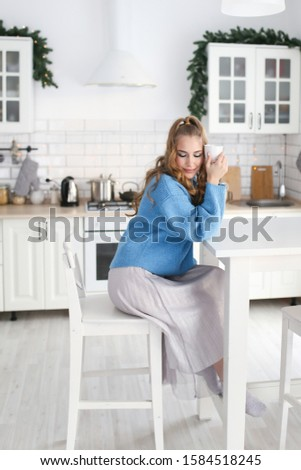 Portrait of a beautiful sweet attractive curly haired girl with long hair in a soft warm blue sweater on the background of a spacious bright white kitchen in a cozy house. #1584518245