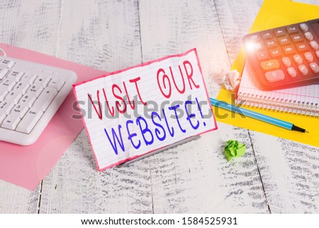 Conceptual hand writing showing Visit Our Website. Business photo showcasing visitor who arrives at web site and proceeds to browse Notepaper on wire in between computer keyboard and sheets. #1584525931
