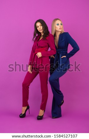 high fashion style two attractive women on violet background in stylish colorful evening suits of purple and blue color, friends having fun together, fashion trend #1584527107