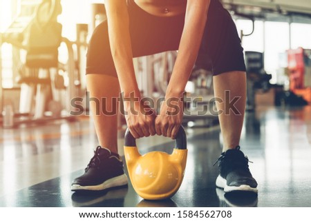 Lifestyle Beautiful young woman in class using equipment dumbbell weights heavy fit hand her exercise, workout or cardio at fitness GYM #1584562708