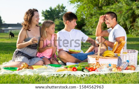 Parents with two teenagers enjoying  delicious meal on the picnic #1584562963