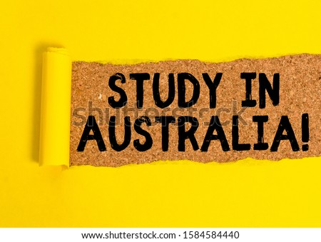 Word writing text Study In Australia. Business concept for going into foreign country order complete your studies Cardboard which is torn in the middle placed above a wooden classic table. #1584584440