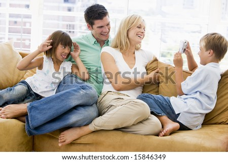 Family sitting in living room with digital camera smiling #15846349