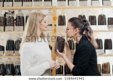 A female shopper in the store chooses a grain coffee. The seller helps the buyer choose. #1584641941