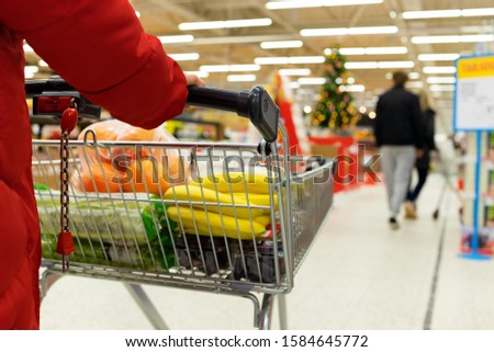 Woman with a basket walks in a supermarket. Hand and part of the basket in focus, blurred background #1584645772