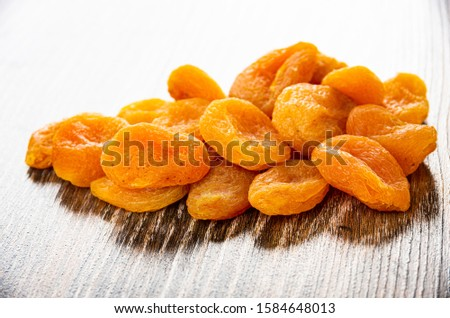Heap of dried apricots on dark wooden table #1584648013