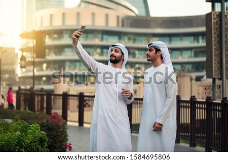 two arab young man taking selfie in dubai streets