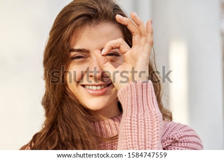 Facial expression and human emotions, body language. Close-up portrait of young brunette. Cheerful positive blonde girl laughs shows OK sign. Girl with green eyes long curly hair wearing pink sweater #1584747559