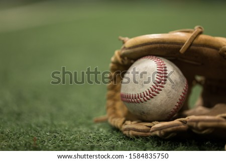 Close up of baseball in mitt on turf Royalty-Free Stock Photo #1584835750