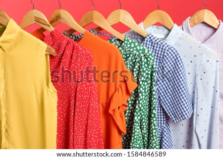 Bright clothes on hangers against red background, closeup. Rainbow colors #1584846589