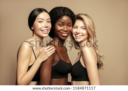 Beauty. Multi Ethnic Group of Womans with diffrent types of skin together and looking on camera. Diverse ethnicity women - Caucasian, African and Asian posing and smiling against beige background. #1584871117