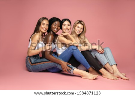 Multi Ethnic Group of Womans with diffrent types of skin sitting together and looking on camera. Diverse ethnicity women - Caucasian, African and Asian against pink background #1584871123