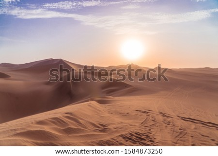 Sandy desert at sunset. Dry, hot sand deserted vibes. Travel, holiday, explore scenic shot, with sand ripples, sun setting and footprints. Tourism shot in Huacachina, Peru. Epic, dramatic shot.  Royalty-Free Stock Photo #1584873250