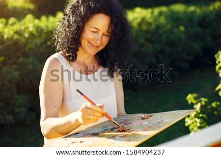 Woman artist painting with oil. Paints in a field #1584904237