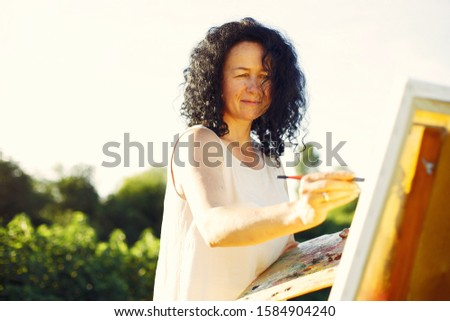 Woman artist painting with oil. Paints in a field #1584904240